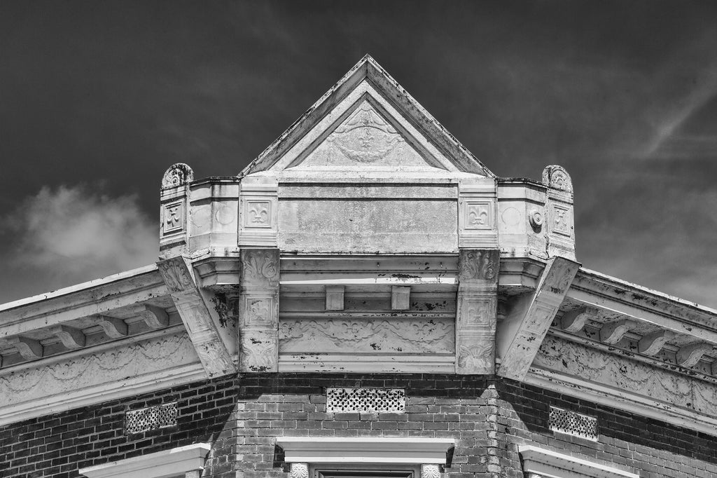 Black and white architectural detail photograph of a decorative antique pressed-tin roofline façade with fleur-de-lis in picturesque Ste. Genevieve, Missouri.