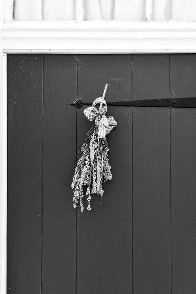 Black and white architectural detail photograph of an old door with a hanging of dried flowers on a historic house in beautiful Ste. Genevieve, Missouri.