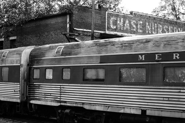 Black and white photograph of a rusty set of retired railroad passenger cars parked on decommissioned railroad tracks outside an abandoned station.