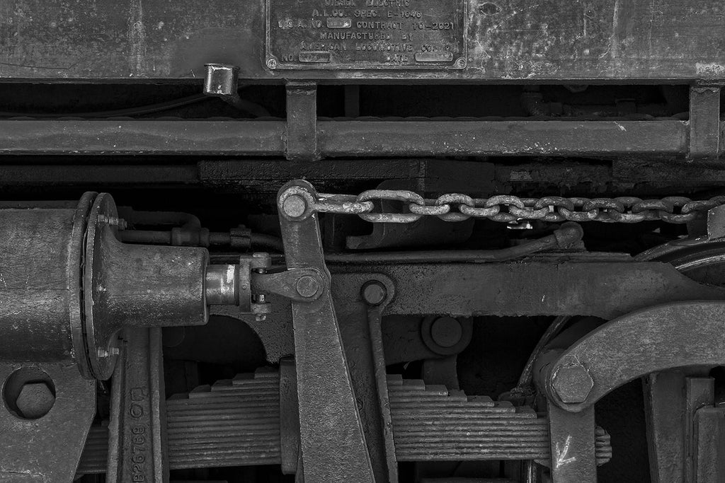 Black and white photograph of the mechanical parts on the undercarriage an old railroad car, creating a black on black tonal effect.