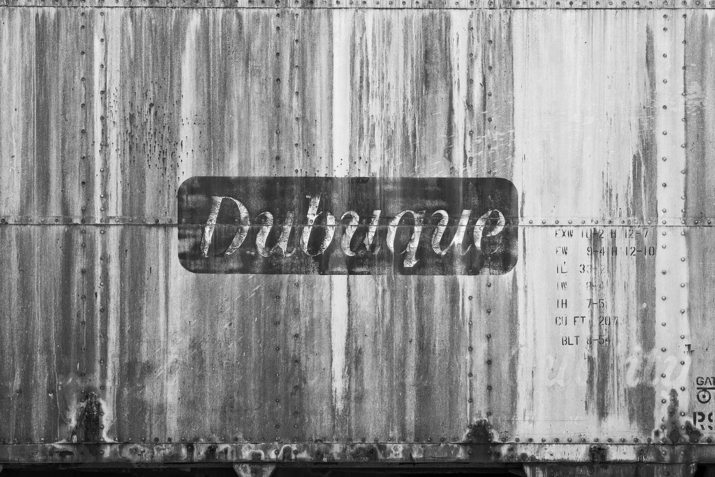 "Black and white photograph of an abandoned antique railroad car with the word ""Dubuque"" painted on its side."