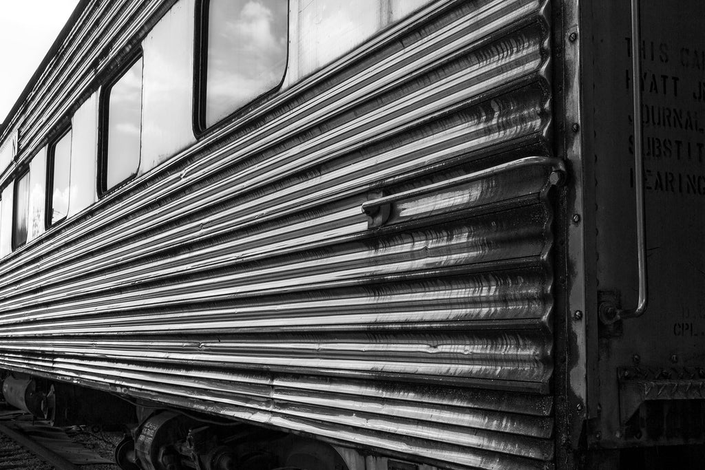 "Black and white photograph of a very shiny metallic ""space age""-style railroad car now retired on the tracks with other rusty old railroad cars."