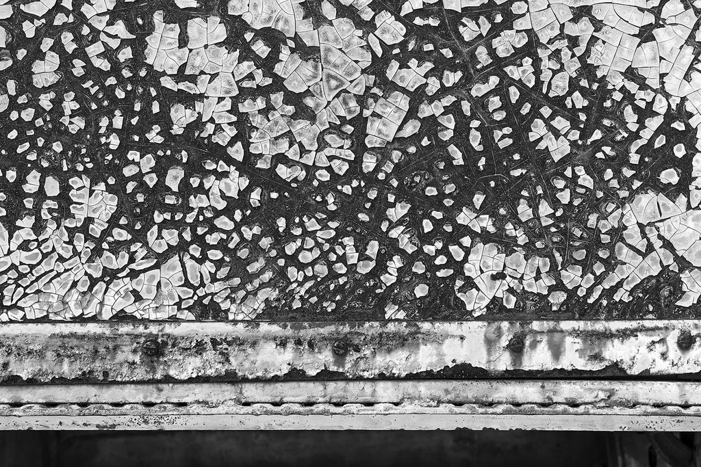Black and white abstract photograph of chipped and peeling paint on the rusty metal exterior of an abandoned vintage railroad dining car.