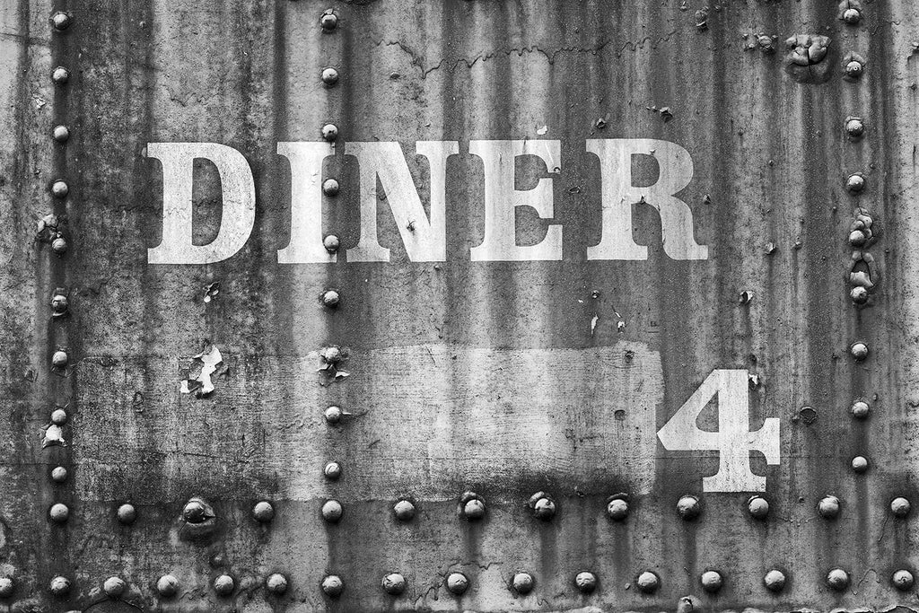 "Black and white photograph of an abandoned railroad dining train car with the words ""Diner 4"" on its exterior wall"