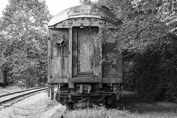 Black and white photograph of an abandoned and rusty old train car sitting on railroad tracks among the trees.