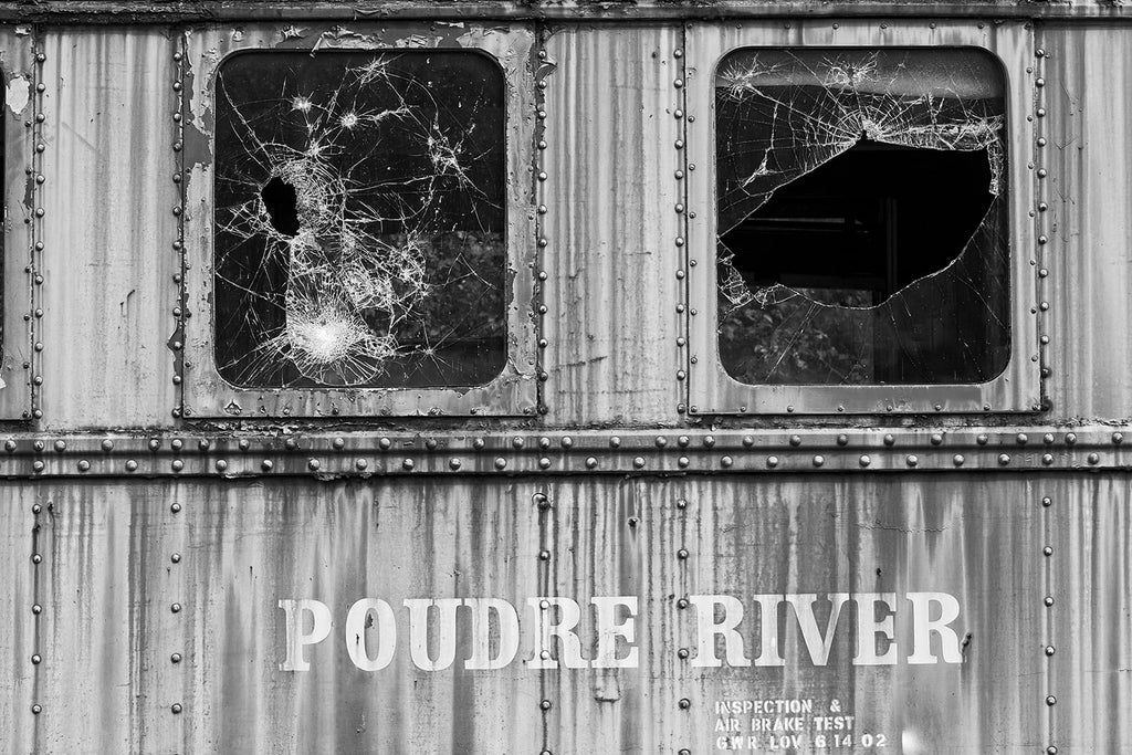 "Black and white photograph of an abandoned railroad dining train car with shattered window glass. The side of the car displays the words ""Poudre River,"" which runs through the US state of Colorado."