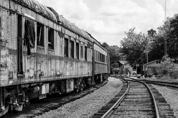 Black and white Photo of Rusty Abandoned Trains Sitting on Railroad Tracks