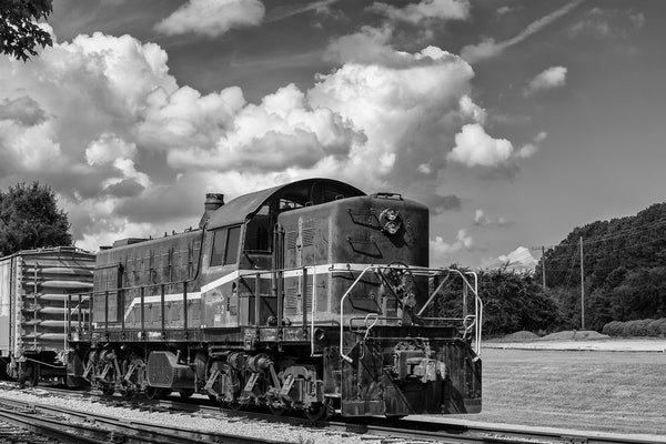 Black and white photograph of an retired old train locomotive sitting on railroad tracks among the trees.