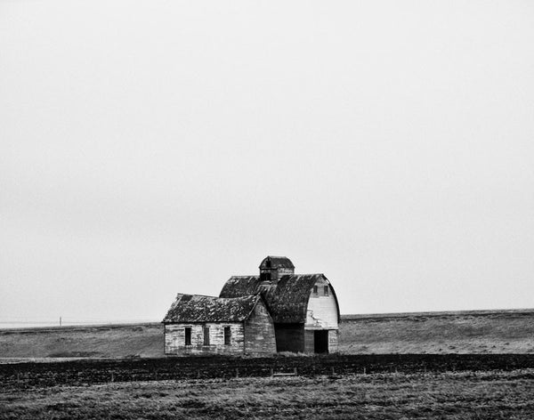 Black and white landscape photograph of an abandoned barn and farmhouse on the cold Minnesota prairie.