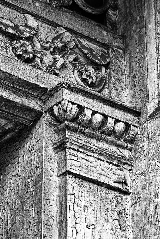Black and white architectural detail photograph of beautifully decorative woodwork on the front of a big abandoned white house in New Orleans.