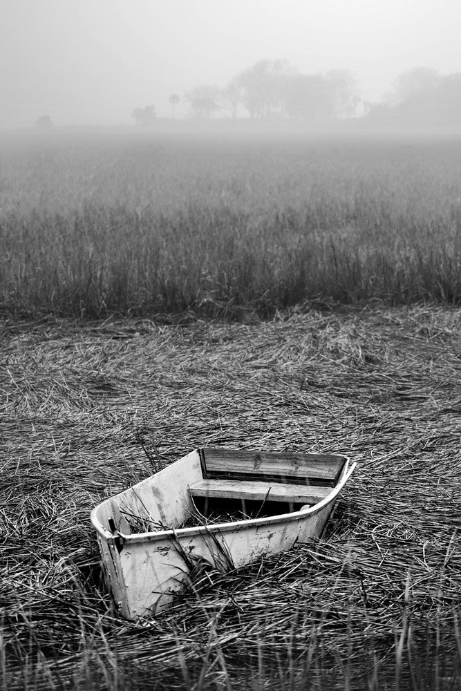 Black and white photograph of an abandoned boat on the reeds of a Charleston marsh at low tide.