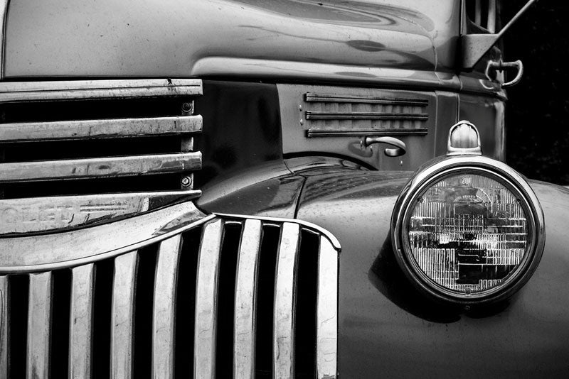 Black and white fine art photograph of the stylish curves around the grill and headlight of a vintage 1947 Chevrolet.