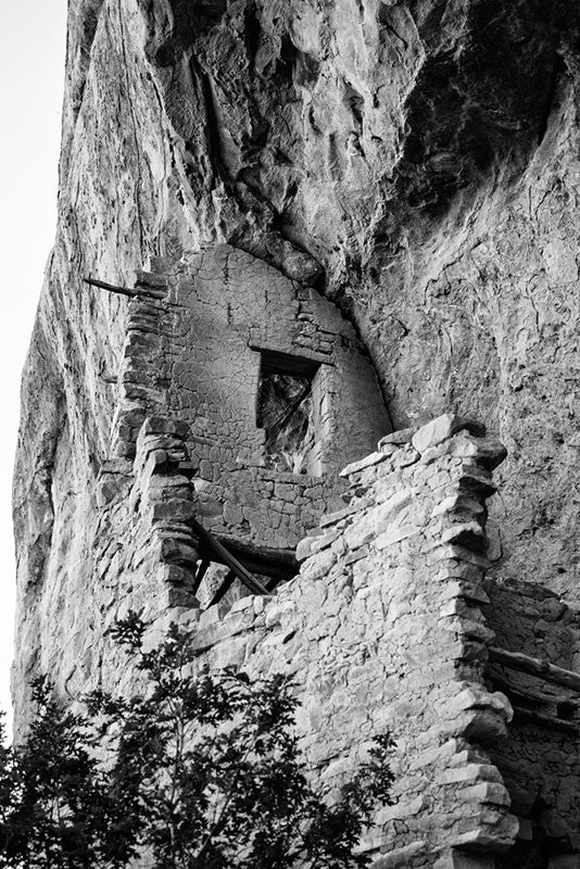 Black and white fine art photograph looking up at ancient walls built into the mesa wall at Mesa Verde, Colorado.