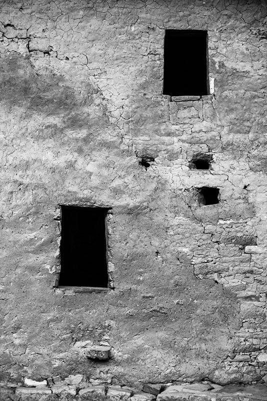 Black and white fine art photograph of a beautifully textured wall with two windows at the ancient Native American dwellings at Mesa Verde in Colorado.