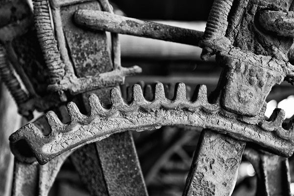 Black and white photograph of the gear mechanism of an antique farm tractor, which is still caked with the dried mud of the fields where it once worked.
