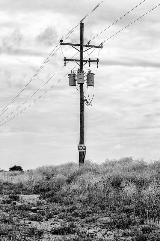 "Black and white photograph of a telephone pole in the Texas Panhandle with a small sign that says, ""BIG."""
