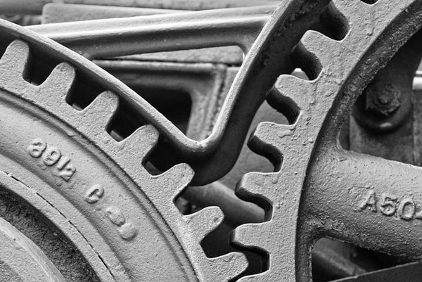 Black and white photograph of large gear wheels with big teeth in an antique machine.