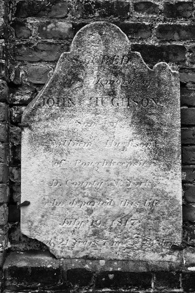 Black and white photograph of a broken old headstone in Savannah's historic Colonial Cemetery. Established in 1750, the burial ground expanded to six acres and was closed to interments in 1853. It now serves as a public park in Savannah's historic district.
