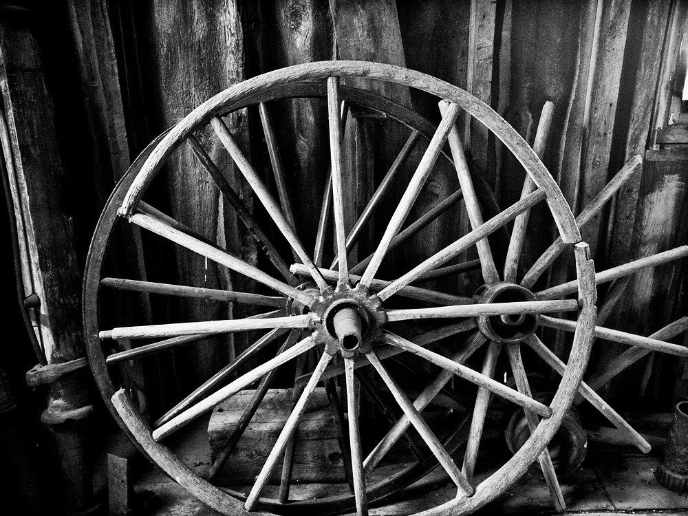 Black and white photograph of a broken antique wagon wheel found inside a wooden barn.
