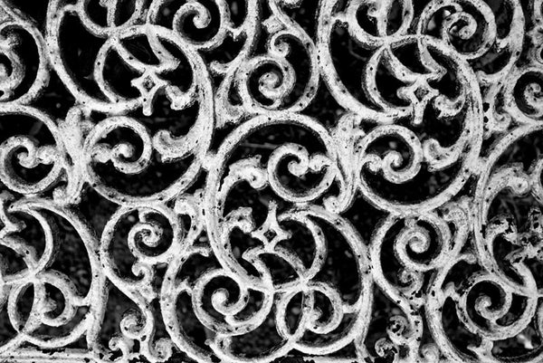 Black and white detail photograph of a white cast iron bench in an unkept section of Savannah's famous, beautiful, and creepy Bonaventure Cemetery.