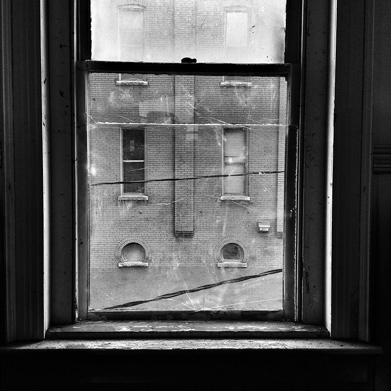 Black and white photograph looking through an old window from the second story of a historic building on Charlotte Avenue in Nashville. This view of another old building across the street, must be similar to what one would have seen from the same window 100 years ago.