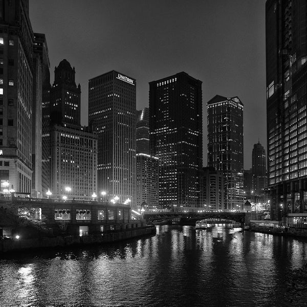 Black and white photograph of the downtown Chicago skyline at night, with city lights reflecting in the black Chicago River.
