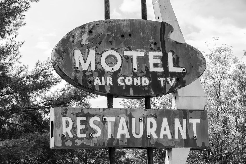 "Black and white photograph of a fading, vintage Motel sign that has been repainted, increasing the texture and patina of its surface. The sign says ""Motel - Air Cond - TV - Restaurant."""