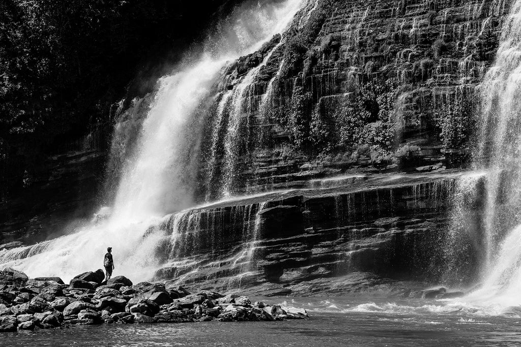 Moody black and white landscape photograph of dramatic waterfalls with a person in foreground providing a sense of scale.