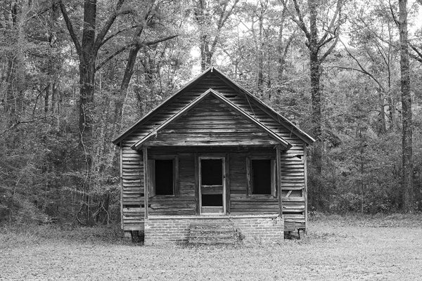 Black and white photograph of a long-abandoned little wooden schoolhouse still standing in the woods.