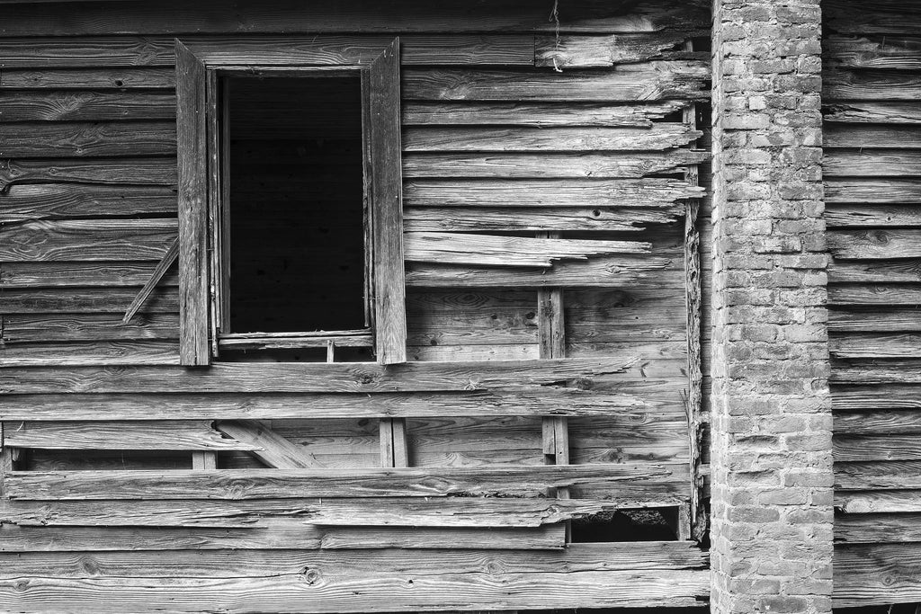 Black and white photograph of the weathered and broken wood and brick remnants of an abandoned old house. This photograph is a study in proportions and textures.