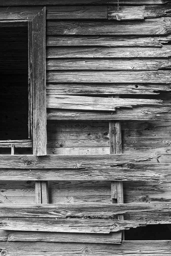 Black and white detail photograph of beautifully textured and weathered wood on the exterior of an abandoned old house.