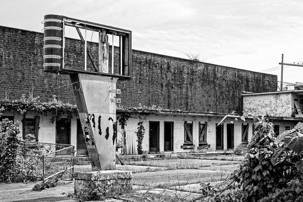 Black and white photograph of an abandoned motel with a broken sign in the Mississippi Delta