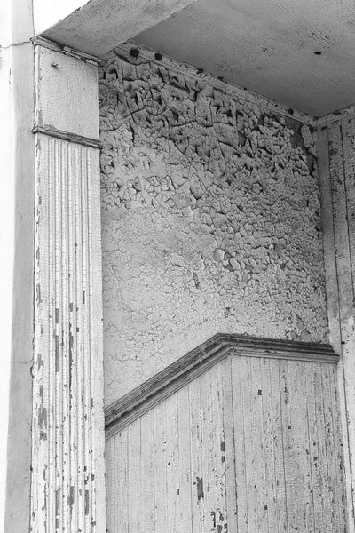 Black and white detail photograph of cracked and peeling paint on the entry to a historic building in downtown Selma, Alabama.