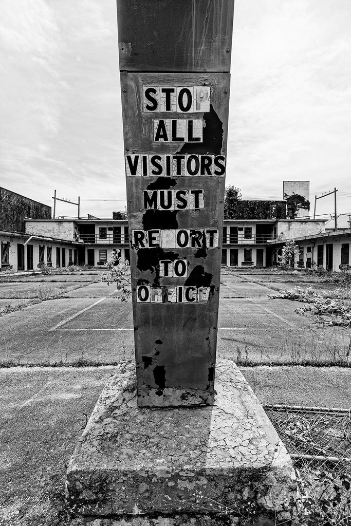 "Black and white photograph of an abandoned motel with message on the post of its old sign that says ""Stop All Visitors Must Report to Office."""