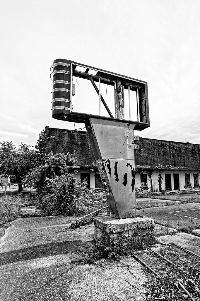 Black and white photograph of a broken old sign on the edge of a parking lot at an abandoned motel in the Mississippi Delta.