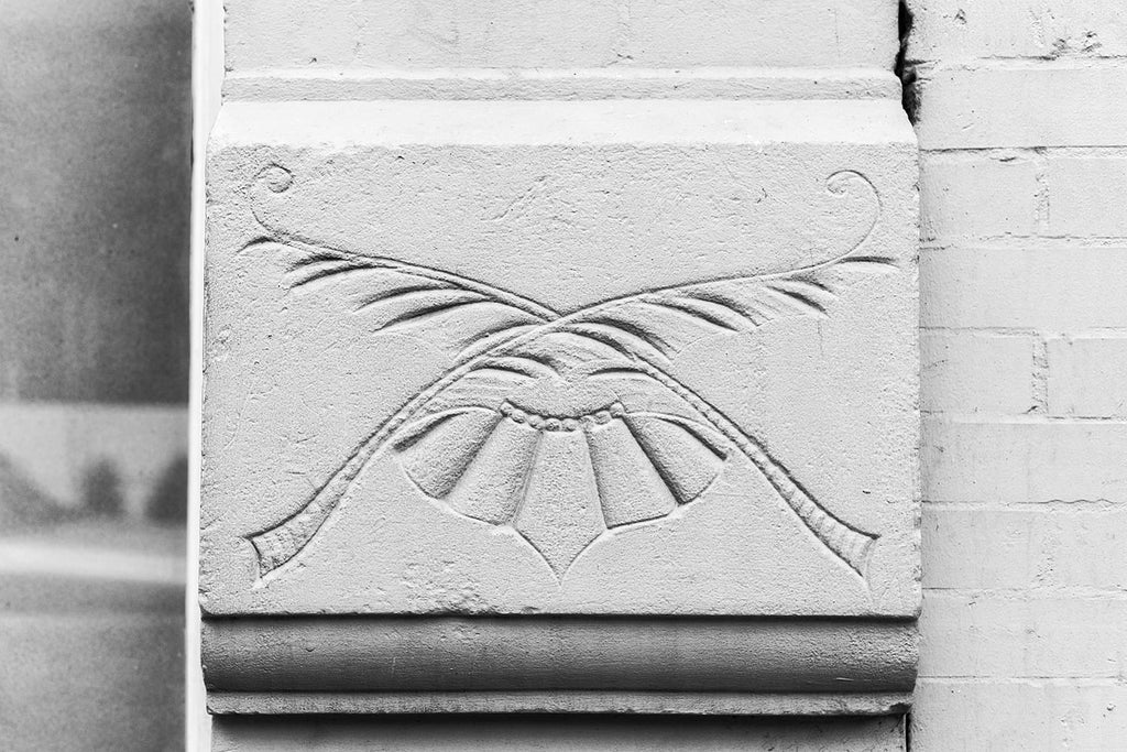 Black and white photograph an architectural detail of a floral impression in the exterior of a historic building in Nashville.