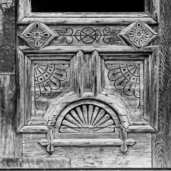 Black and white fine art photograph of a weathered old wooden door with fancy design patterns. (Square format)