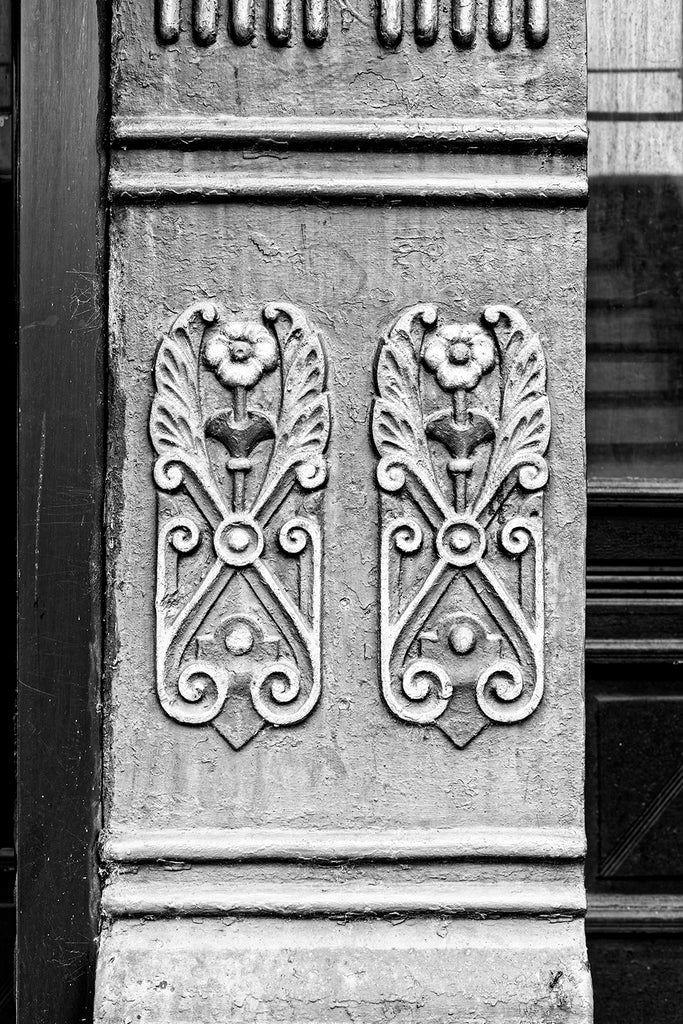 Black and white photograph of ornate cast iron flowers seen on an old building on the main street of a small town.