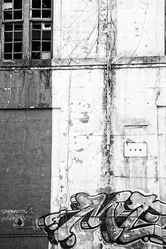 Black and white photograph of the wall of an abandoned building with graffiti and broken windows. Vertical composition.