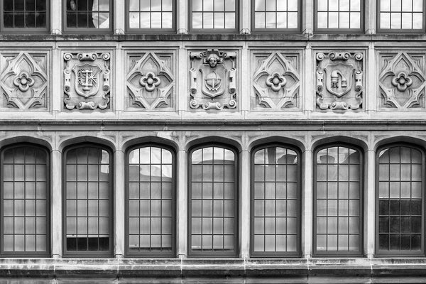 Black and white photograph of the carved stone symbols over the front entrance to Nashville's historic Hume-Fogg High School, which merged from two schools in 1912, with roots back to 1855. Hume-Fogg's notable alumni include the late entertainer Dinah Shore and 1950s pin-up model Bettie Page.