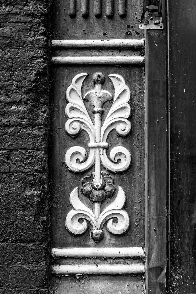 Black and white photograph of an ornate cast iron architectural detail seen on the main street of a small town.