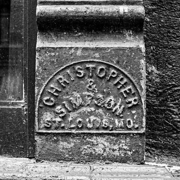 Black and white photograph of an antique name plate for Christopher & Simpson, a St. Louis-based company that manufactured cast iron storefronts that can still be seen on the main streets of many small towns across America. (Square format)