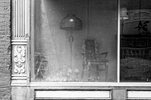 Black and white photograph of old furniture arranged behind hazy glass in the window display of a main street shop in a small town.