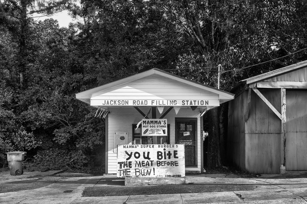 "Black and white photograph of an old filling station turned into a hamburger and hot dog stand in Vicksburg, Mississippi. The hand-painted sign in front reads, ""You bite the meat before the bun!"""