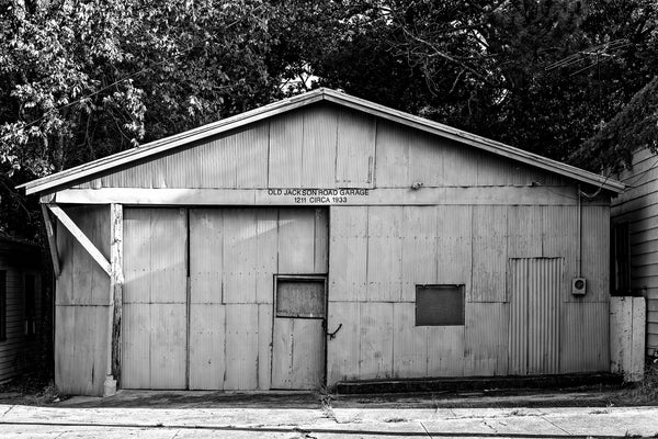 "Black and white photograph of an old garage building with a sign that says ""Old Jackson Road Garage, Circa 1933."""