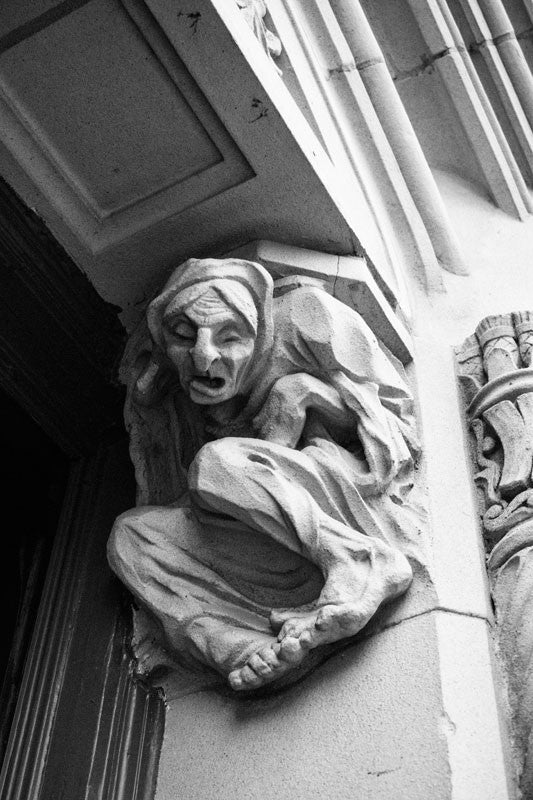Black and white fine art architectural photograph of a wretched gargoyle figure in the street level doorway of The Emily Morgan Hotel in San Antonio, Texas.