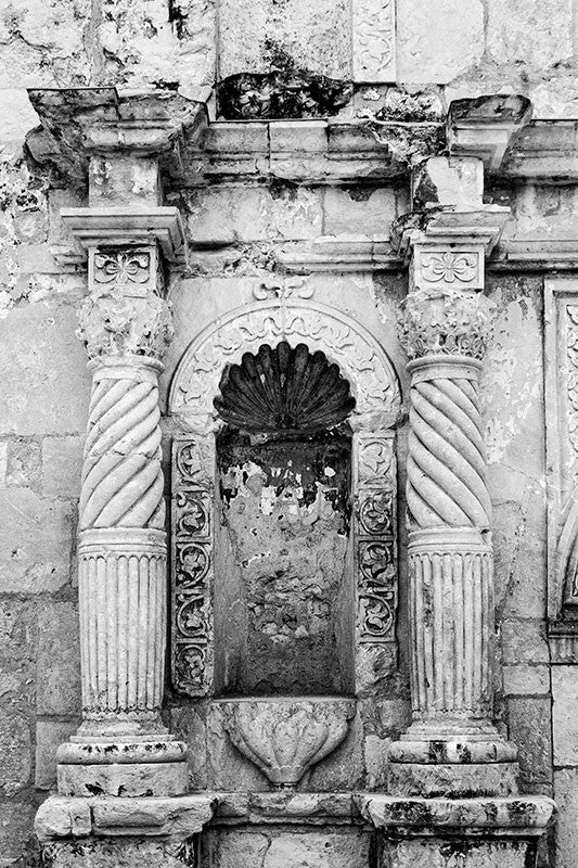 Black and white architectural detail photograph of the carved stone columns on the front of the world-famous Alamo.