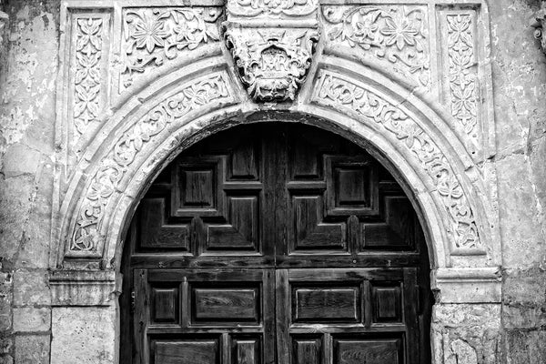 Black and white photograph of the arch over the entrance to the world-famous Alamo, cradle of Texas independence from Mexico in San Antonio, Texas. This architectural detail photograph illustrates the ornate stone carvings and textures of the building, which began existence as a Spanish mission in 1744, known originally as Misión San Antonio de Valero.