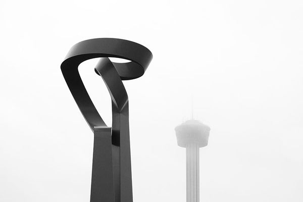 "Black and white photograph of two of San Antonio's most iconic landmarks on a foggy morning -- San Antonio's big, red sculpture ""La Antorcha de la Amistad"" (The Torch of Friendship) by Mexican artist Sebastian, and in the distance, shrouded in fog, is Tower of the Americas."