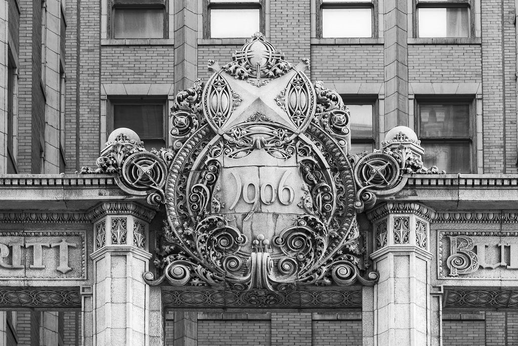 "Black and white fine art photograph of the meticulously ornate Edwardian-style ""1906"" Sign on the exterior of downtown Kansas City's Scarritt Building."